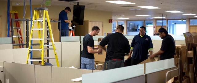 Workers assemble office furniture in the Fred Hutchinson Communications Dept. newsroom on Friday, Oct. 11, 2013.