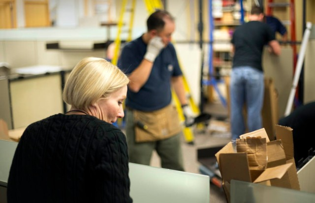 Susan Edmonds checks on the installation of her newsroom desk.