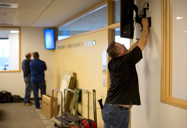 Workers configure one of the wall-mounted monitors while another one is put in place.